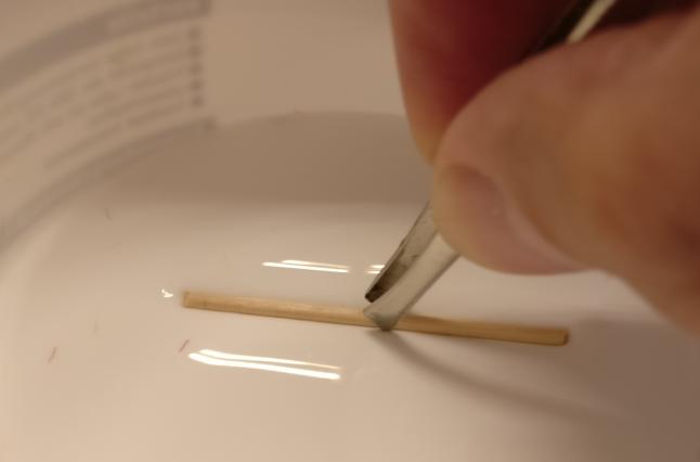 Zum Ankleben der Randhölzer aus Zahnstochern und Schaschlikspießen tunke ich die kurzen Stücke mittels der Pinzette kurz in PONAL.
