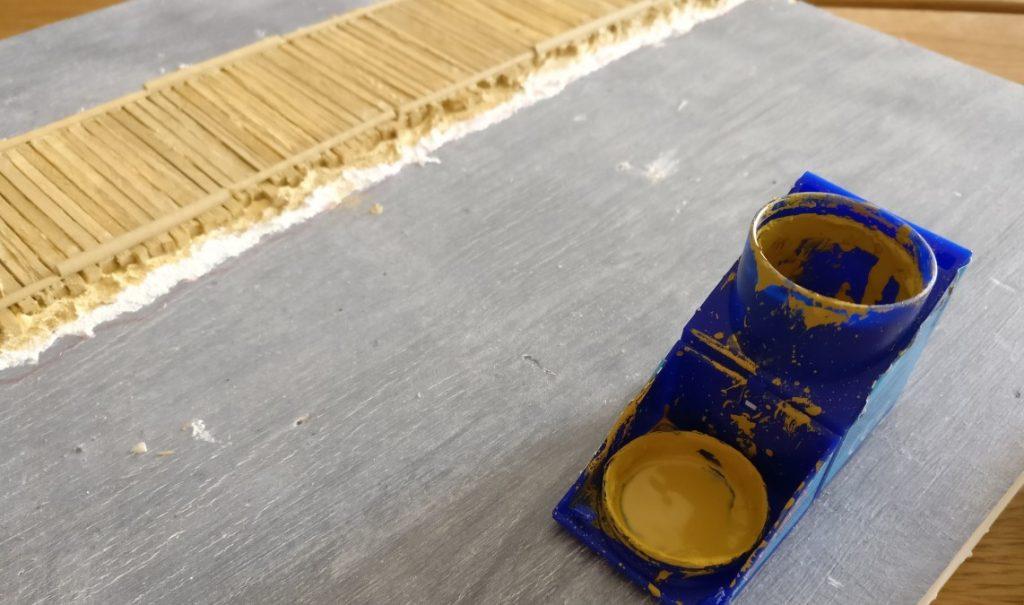 """Mit der Revell Aquacolor 36116 Sand wird die Erdscholle unter den Balken bemalt. Auch der direkte """"Uferbereich"""" wird mit Sand gefärbt."""