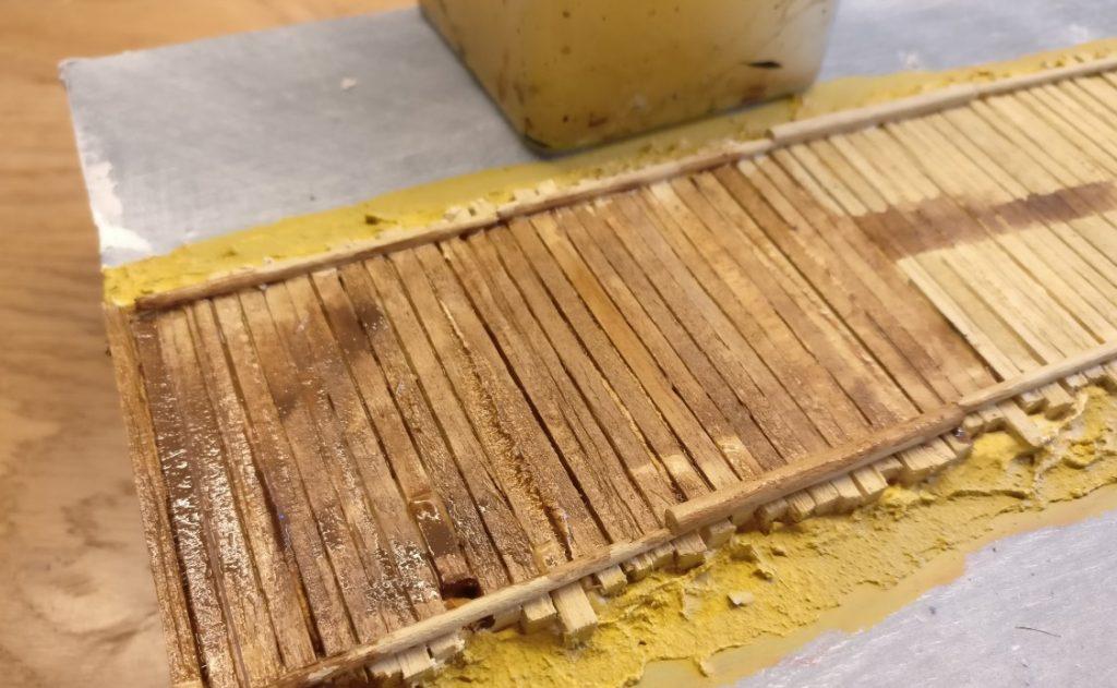 Erster Auftrag der Lasur aus Revell Aquacolor 36184 Lederbraun. Das Holz der Balken und der Untergrund saugen die Feuchtigkeit der Lasur schnell auf. Es muss viel Wasser zugegeben werden, damit die Farbe verarbeitet werden kann.