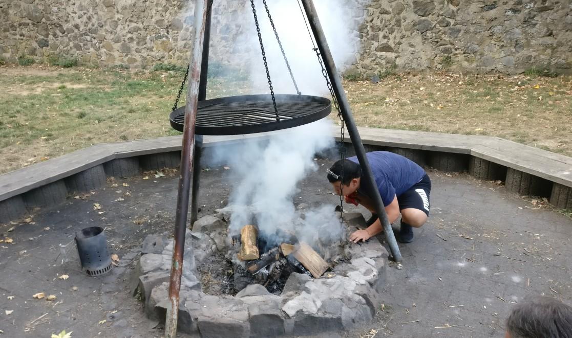 Uni beim Anfachen des Feuers.