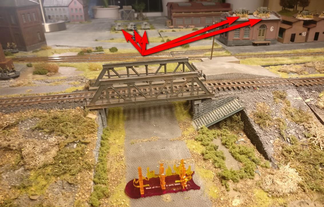 Der transparente orange-rote Feuer-Marker zeigt an, wo die Nebelbank zu liegen kommen wird - genau vor der Eisenbahnbrücke des Bahndamms, dem Missionsziel der 7. Panzerdivision. Im Hintergrund erkennt man die Verteidiger, denen mit der Nebelwand die Einsicht in die Werksstraße genommen werden soll.