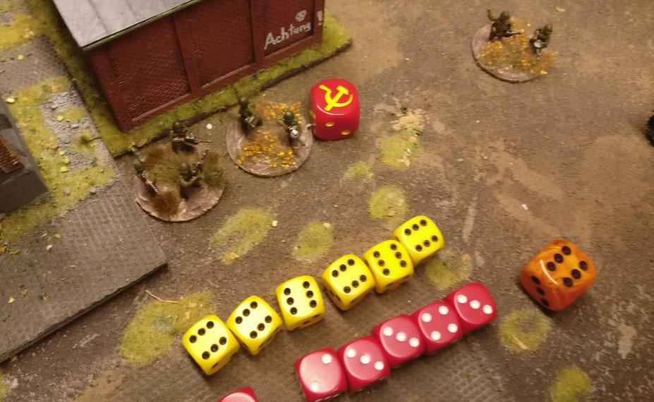 """Der Beschuss erzielte 6 Treffer. Der Verteidiger würfelte mit 6 W6 Würfeln zum Saven dagegen. Dabei fiel eine """"1"""". Fünf Treffer wurden also gesaved, ein Treffer nicht. Eine Foot Group wird entfernt und durch einen Casualty Marker ersetzt. Als Casualty Marker dient ein roter Würfel mit Hammer und Sichel. Der orangefarbene Würfel wurde als Choice-Würfel mitgewürfelt. Der Choice-Wurf """"6"""" erlaubte dem schießenden Spieler die Wahl der getroffenen Foot Group."""
