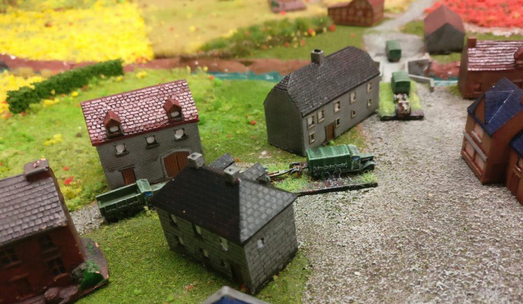 Eine Szene im Ort. Eine Kolonne passiert das Dorf.