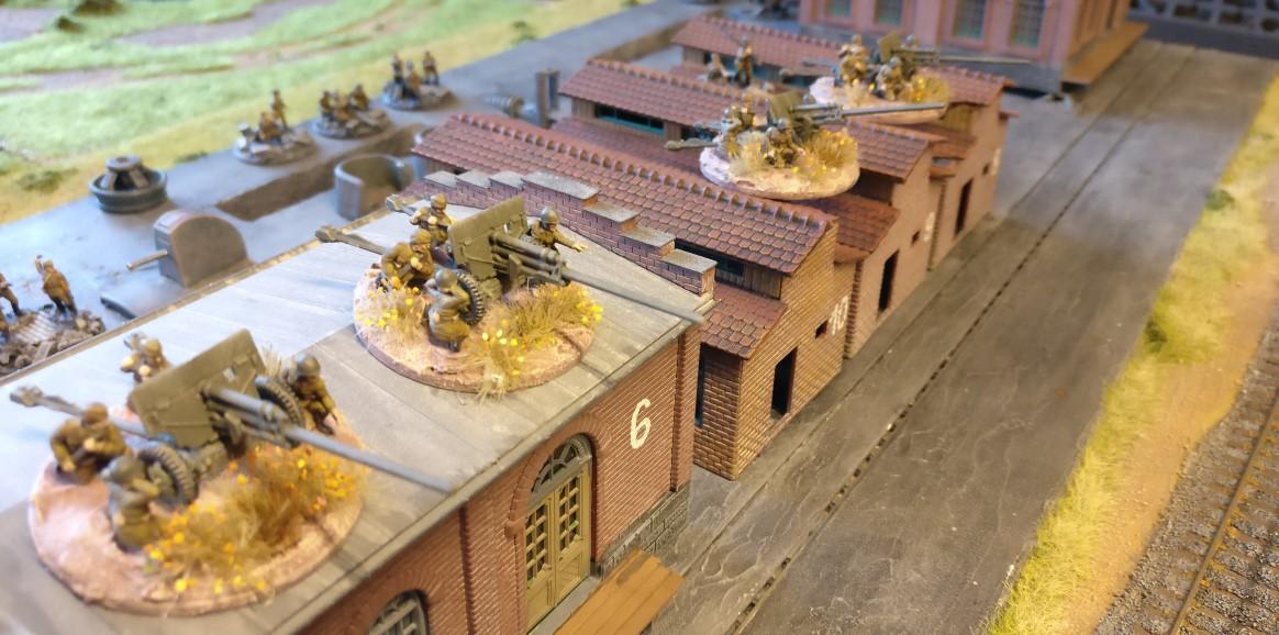 """Die vier 57mm-Pak der zweiten Verteidigungslinie. Die Pak können den gesamten Bahndamm bestreichen, sowie eine Werksstraße vollständig und die andere zum großen Teil. PBI/Poor Bloody Infantry Game """"Wjasma"""": 30. Armee der Roten Armee vs. 7. Panzerdivision der Deutschen Wehrmacht"""