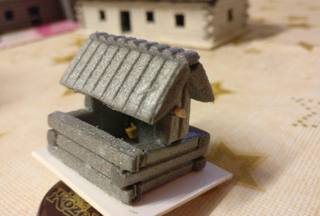 Das Modell des Ziehbrunnens mit Dach über dem Brunnenschacht. Es ist wohl ein Holzkastenbrunnen.