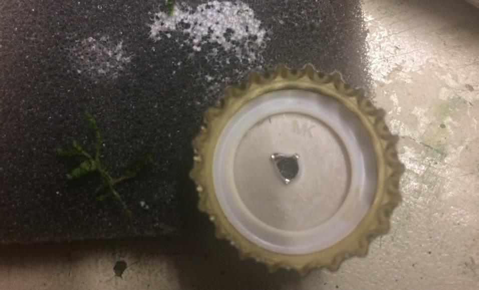 Ein Loch kommt in den Kronkorken