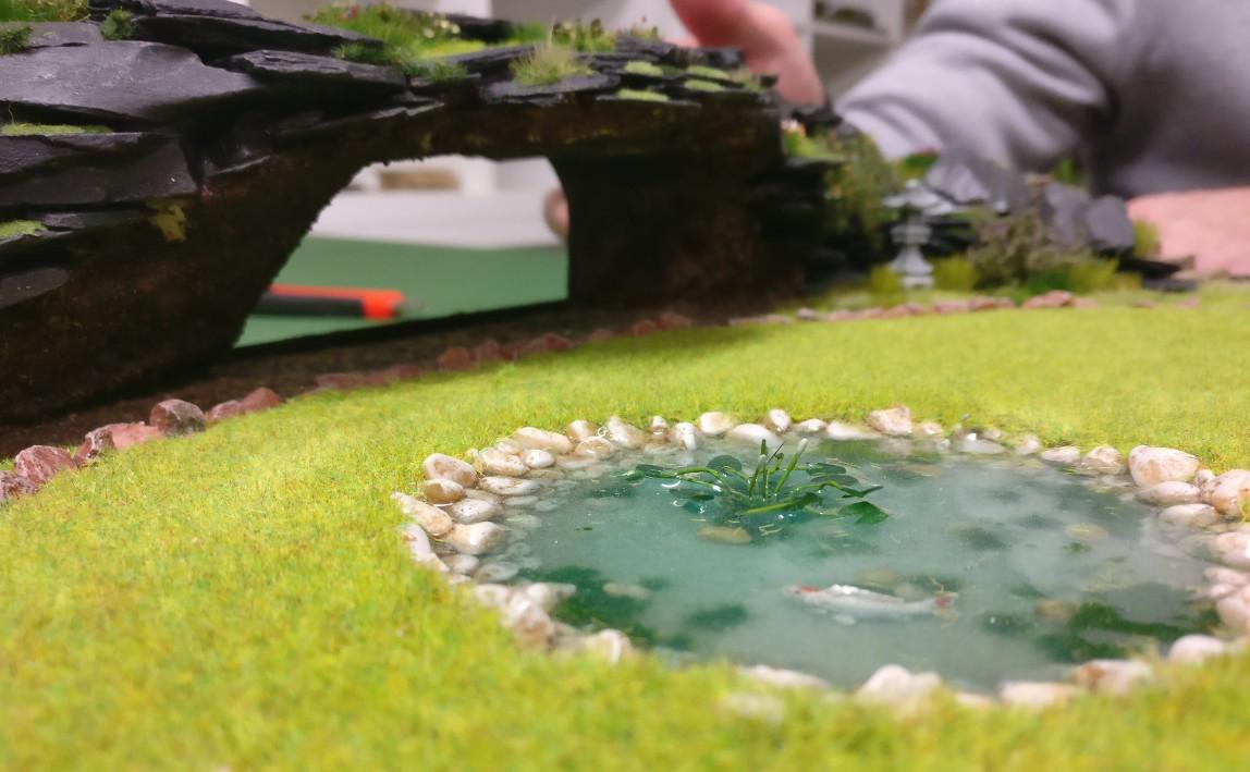 """Blick über den Teich auf die Grotte auf der Bushido-Spielplatte """"japanischer Garten"""" der Ad Arma."""