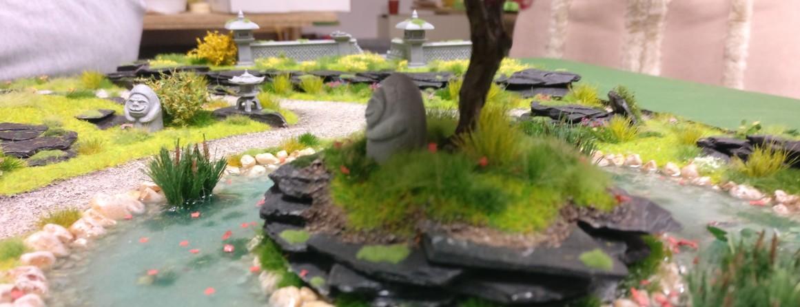 """Gesichterstatuen aus Stein  auf der Bushido-Spielplatte """"japanischer Garten"""" der Ad Arma."""