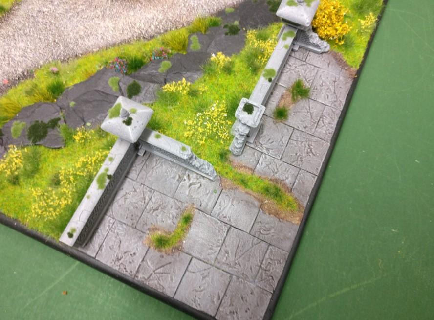 """Die Steinterrasse mit einer Mauereinfassung auf der Bushido-Spielplatte """"japanischer Garten"""" der Ad Arma."""