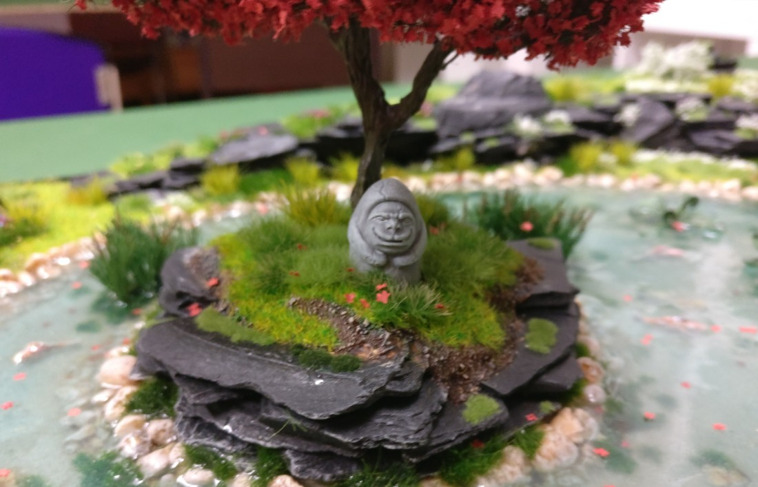 """Eines der Gesichter auf der Steinstatue auf der Bushido-Spielplatte """"japanischer Garten"""" der Ad Arma."""