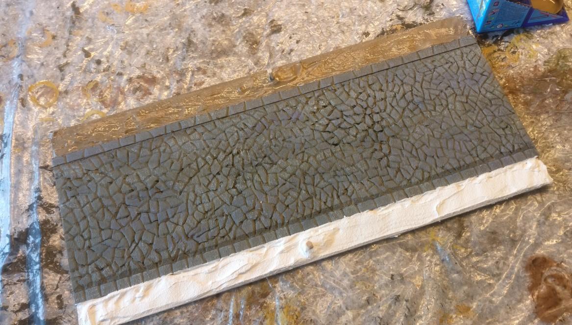 """Beiderseits der römischen Straße wurde mit Strukturpaste ein wenig Erdboden angefüllt. """"Erdfarbe"""" wurde bereits aufgetragen."""