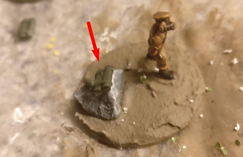 """Hier musste ich den Fels als Sitz einer der """"sitzenden Figuren"""" künstlich erhöhen. Das lag darin begründet, dass die Beine der sitzenden Figur schlicht zu lange waren, als dass sie in zwangsweise schräg sitzender Pose noch natürlich gewirkt hätte. Ich wählte einen der verfügbaren Ausrüstungsgegenstände und klebte ihn auf den Felsen."""