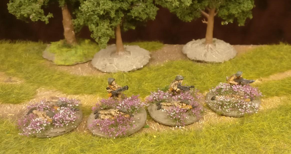 Die LMG-Bases des Flames of War British Infantry Platoon erhielten Violett/weiße Blumenteppiche, zwischen denen die LMG-Schützen stehen.
