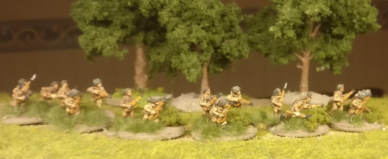 Einge der Rifle Foot Groups des Flames of War British Infantry Platoon erhielten Grasbüschel von MiniNatur und Clump Foliage von Woodland Scenics auf die Base.