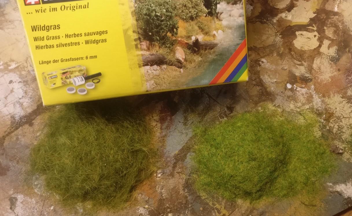 NOCH Wildgras aus dem Handel für Modellbahnzubehör wird auf die Base für die 15mm British Infantry gepflanzt. Der NOCH Gras-Master (ein elektrostatisches Hilfsgerät) sorgt für den aufrechten Stand der Grashalme. Links seht ihr 6 mm Grashalmlänge und rechts seht ihr 2,5 mm Grashalmlänge.