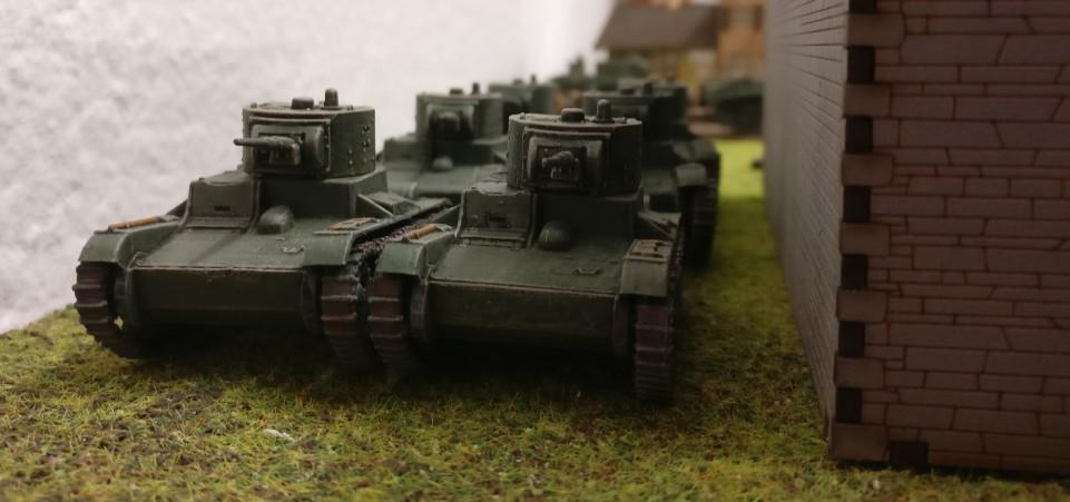 Hinter dem Gebäude stehen sechs leichte Panzer T-26 in Deckung.
