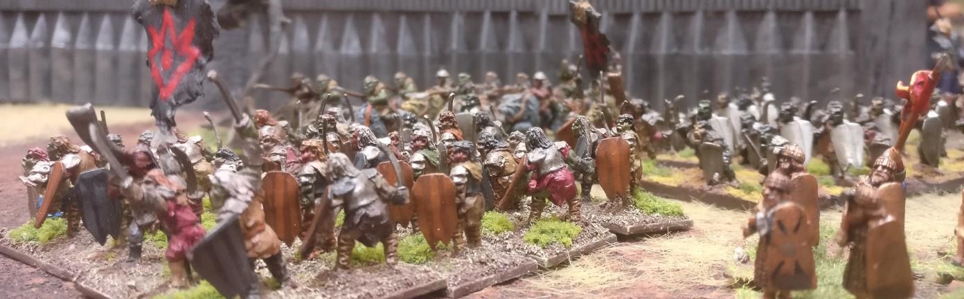Dunkle Horden und Trolle marschieren durch das Tor zwischen den Türmen Narchost und Carchost, die  Feuerzahn und der Starke Hauer geheißen.
