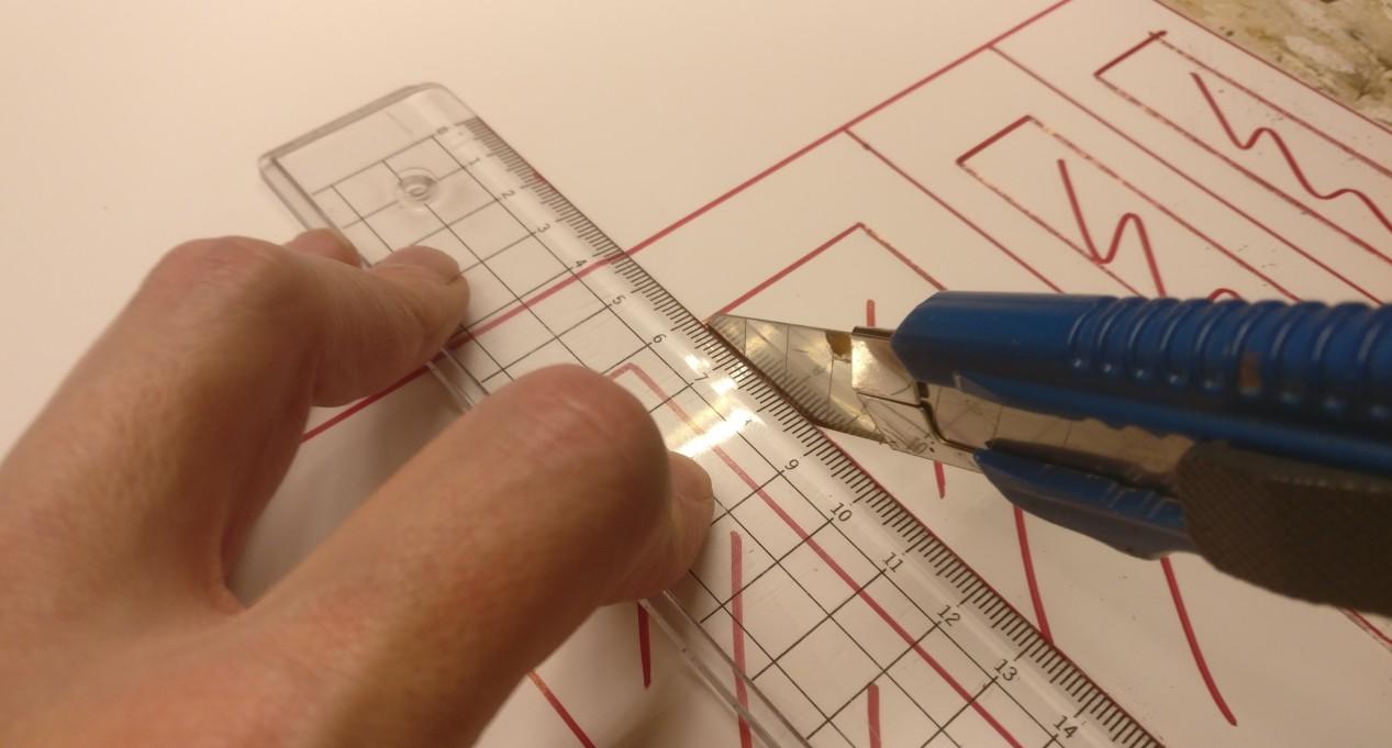 Fertigen der Fertigungshalle: Mit dem Bastelmesser werden die Fenster und Tore aus dem  Foamboard geschnitten. Auch die Bauteilkanten werden so geschnitten.