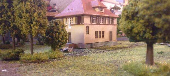 Das Kommandanturgebäude, betrachtet durch das Fernglas von Sergeant Cobbler. Links am Haus erkennbar: ein Drop-Container mit der dringend benötigten Munition für die Ordnance ML 3 inch Mortars
