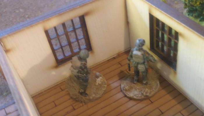 Im Landhaus bezieht ein PIAT-AT-Team Stellung. Die beiden Herren nehmen den Lkw vorm Haus direkt unter Feuer.