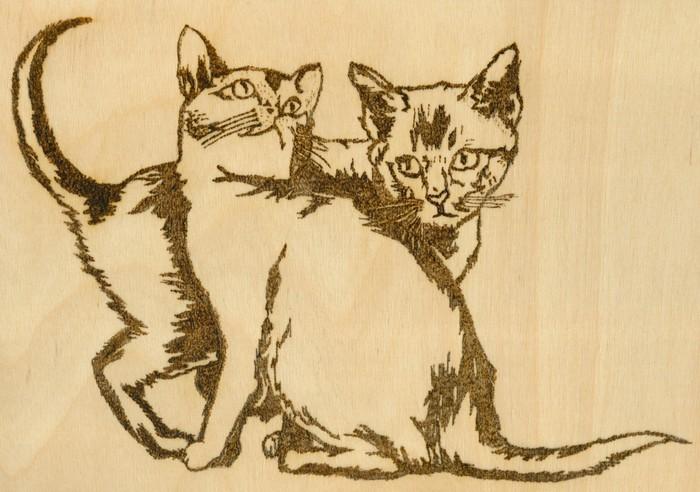 Zwei Katzen als Brennmalerei.