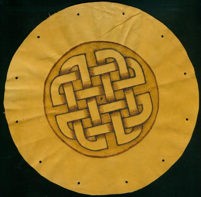 Ein mit Brennmalerei verzierter Lederbeutel. Das Motiv sind keltische Herzen.