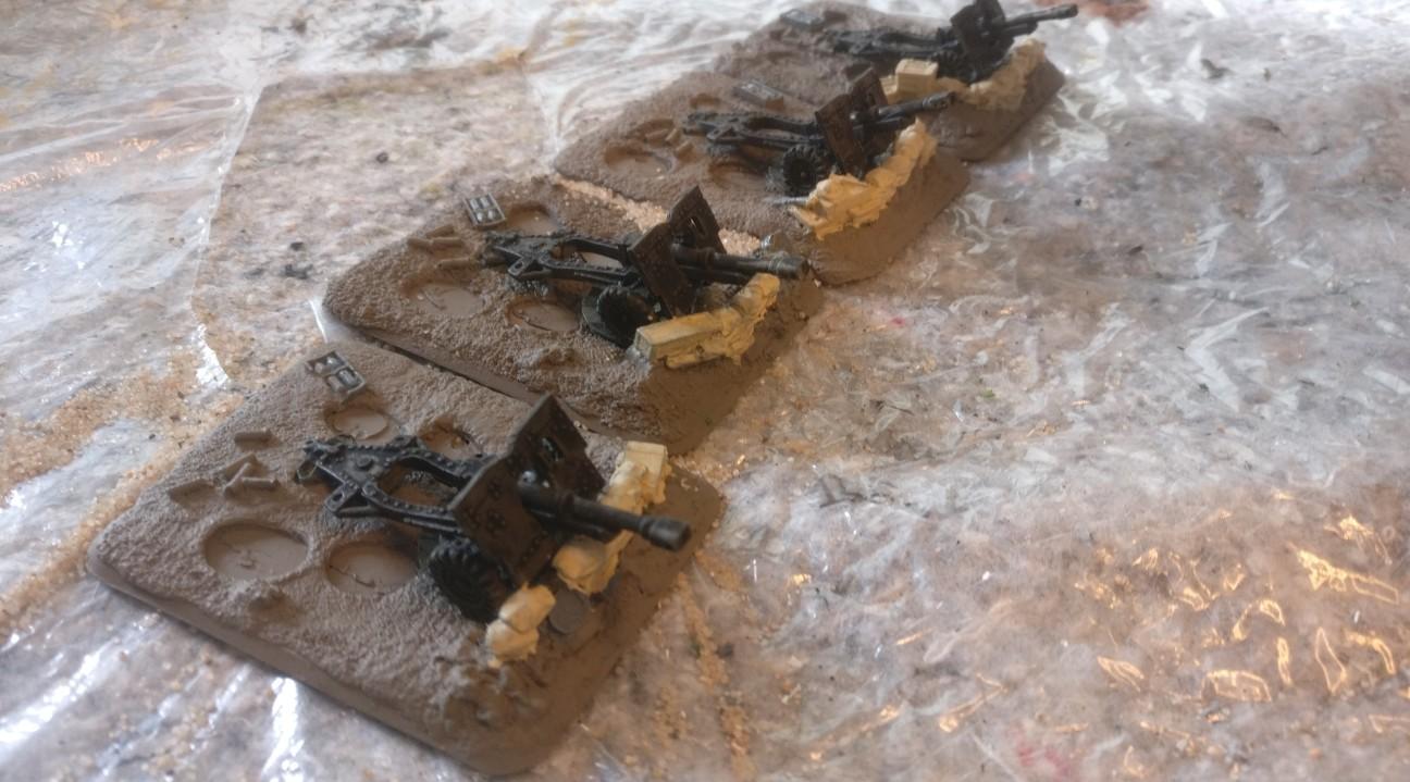 """Die Bemalung der Basen der FoW Royal Artillery Battery erfolgte in Schritten. Hier wurde die Base mit """"Erdfarbe"""" grundiert. Die Sandsäcke und Kisten der Deckung wurden mit 314er Beige bemalt."""