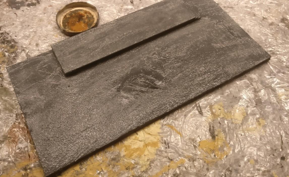 Auf den getrockneten Grundton wird der Wash mit Mittelgrau aufgetragen.