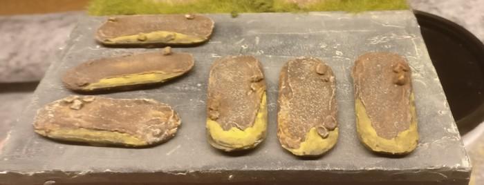 Die seichten Sstellen werden mit einer Lasur aus Revell Aquacolor Gelboliv überzogen. So entstehen vermeintlich tiefe Stellen und ein abfallendes Geländeprofil.