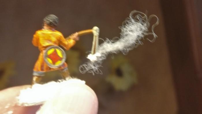 Mit Strukturpaste wird die Base aufgefüttert - und das Feuer dargestellt, welches gleichzeitig den Rauch an der Stockschleuder anheftet.