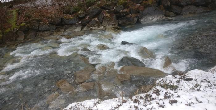 Wenn sich das Wasser über Steine in die Tiefe stürzt, spritzt die Gischt weiß auf.
