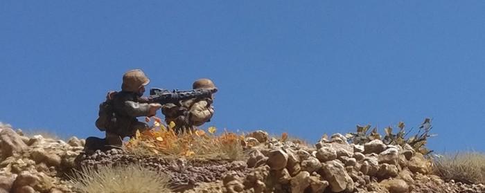 Ein MG-Trupp des Panzergrenadier-Regiment 104 der 21. Panzerdivision nimmt eine britische Stellung bei Tobruk unter Feuer.