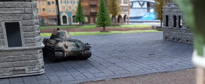 Ein T-34/76 geht hinterm Haus in Stellung.