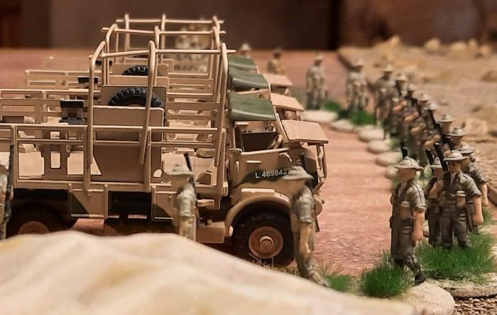 Eine Marschkolonne des 25th Battalion der 7th Division (Australien) neben drei Trucks.
