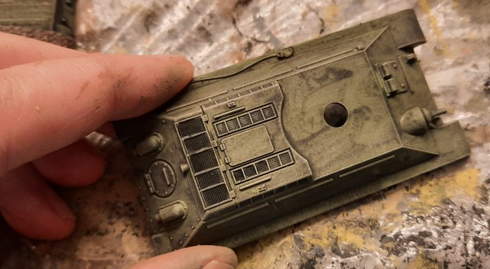 """Die Wannenoberteile werden mit """"Helloliv"""" trockengebürstet. Das hellt die Oberfläche auf und betont erhabene Partien. Die Lüftungsgitter auf dem Panzerheck werden nochmals mit dem Black Wash überzogen. So dunkeln sie nach"""