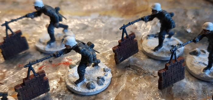 """Hier heben sich die mit Blaugrau bemalten Steine von der Base ab. Die Helme der LMG-Schützen wurden bereits geweißelt und mit einem Schleier von """"Mittelgrau"""" überzogen."""