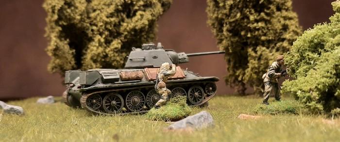 Ein Frontnik mit Maschinenpistole sichert gegen überraschend auftauchende Feindtruppen. Im T-34 beobachtet der Kommandant das Areal.