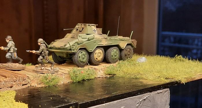 Ein Panzerspähwagen Sd.Kfz. 234/1 mit 2-cm-KwK 38 L/55 fährt auf den Knüppeldamm. Panzergrenadiere des Infanterieregiments 510 sind auch zu Gange,