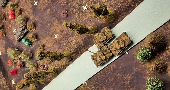 Drei Durchbruchspanzer Tiger I der schweren Panzerabteilung 503 auf der Rollbahn in Richtung Durchbruch nach Obojan. Sie beharken die Stellungen der SU-152 der 27. Kanonenartillerie-Brigade, um den Panzergrenadieren des Panzer-Grenadier-Regiment 110 den Weg freizuschießen.