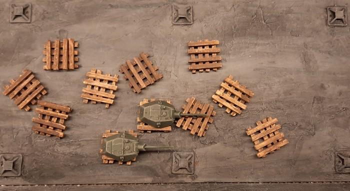"""Die fertig lasierten Holzbalkenstapel mit aufgelegten Panzertürmen in der Produktionshalle 1 der Sawod Nr. 1 """"Roter Oktober"""" in Shturmigrad-Süd"""