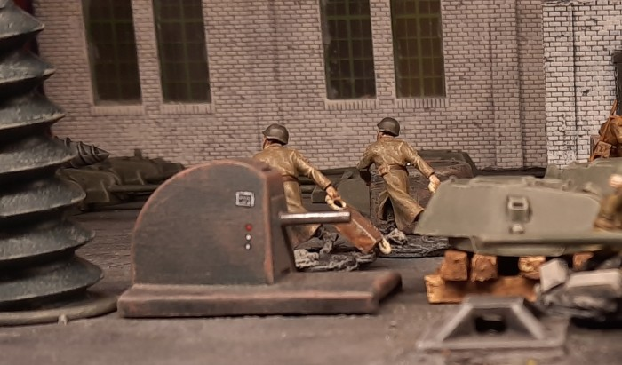 Eilig zerren die Arbeiter (Freiwillige der 44. motorisierten Brigade des 1. Panzerkorps) Kisten mit Werkzeug durch die Halle, um die Montagearbeiter auszustatten.