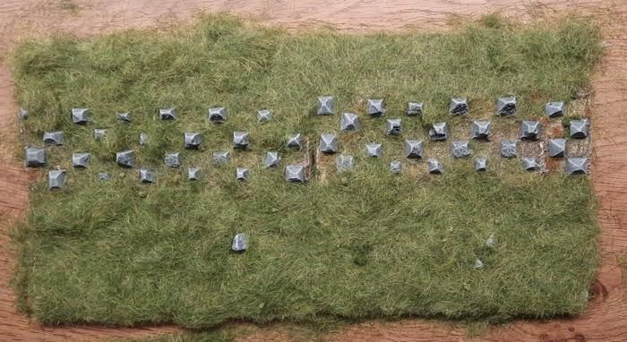 Nun sind die beiden Sarissa-like Terrain Tiles dick mit Streugras eingepackt. Nach dem Trocknen und Abbinden kommen die Drachenzähne beim Entfernen des überschüssigen Streugrases wieder zum Vorschein.