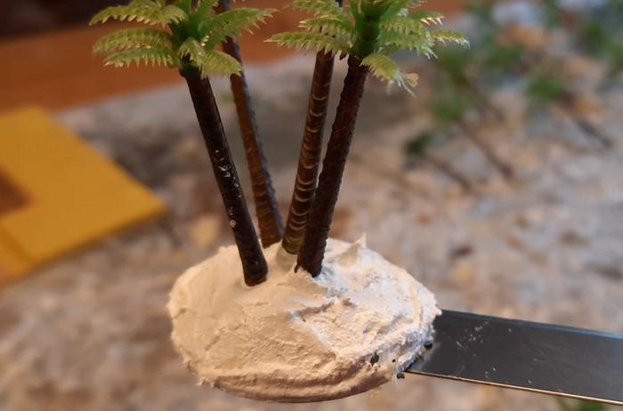 Die Palmen stecken im Erdhügel. Nun muss die Strukturpaste über Nacht aushärten.