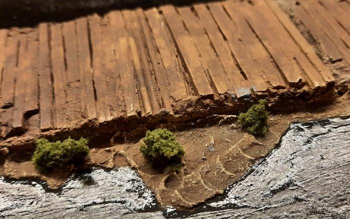 Erste Büsche aus Clump Foliage von Woodland Scenics sind seitlich des Knüppeldamms gepflanzt.