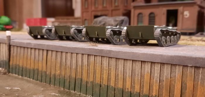 An der Kaimauer stehen die Chassis der T-40 aufgereiht. Sobald die übrigen Bauteile angeliefert werden, kann die Endmontage fortgesetzt werden.