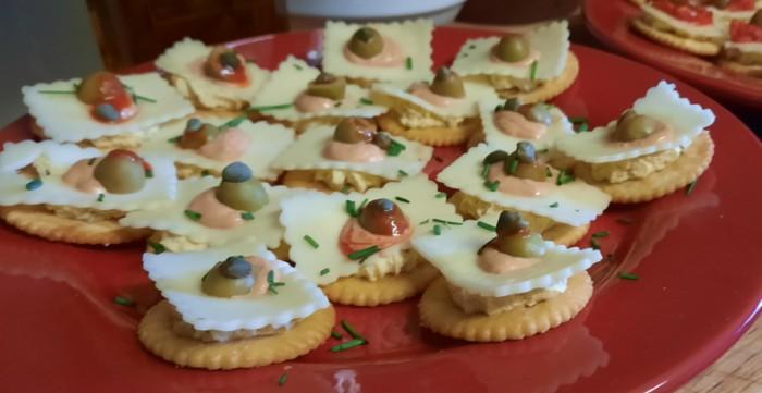 Genauso stilecht auf die Kräcker genagelt: feinsäuberlich zackelig geradelte Käsescheiben mit leckeren Soßen und Kräutern drauf.