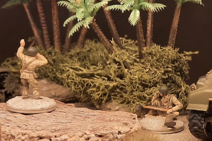 Detailausschnitt: der Offizier und sein Funker. Letzterer ist schlauer und hockt hinter dem Palmenwäldchen in Deckung.